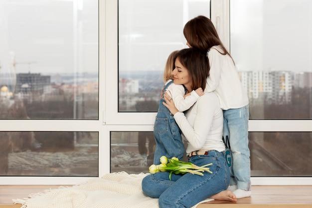 Madre abrazando a hijas