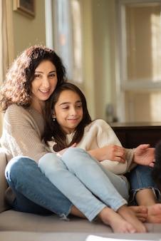 Madre abrazando a su hija en casa