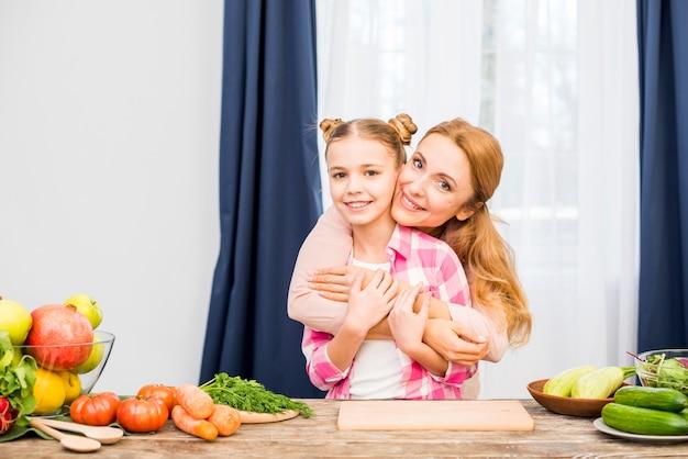 Madre abrazando a su hija de pie detrás de la mesa de madera con verduras frescas