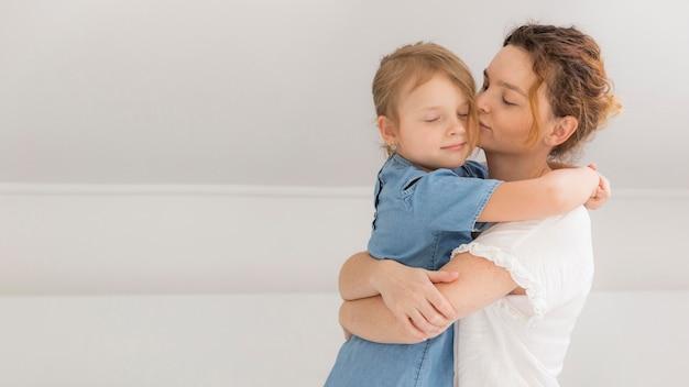 Madre abrazando a su niña en casa