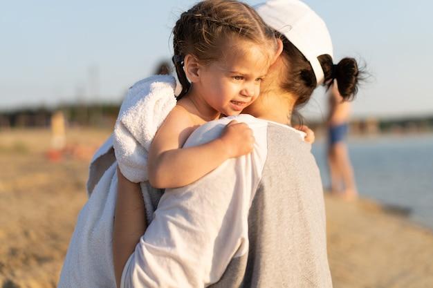 Madre abrazando con su pequeña hija al aire libre en la naturaleza en un día soleado emociones humanas positivas, sentimientos, emociones. retrato de familia feliz en las vacaciones