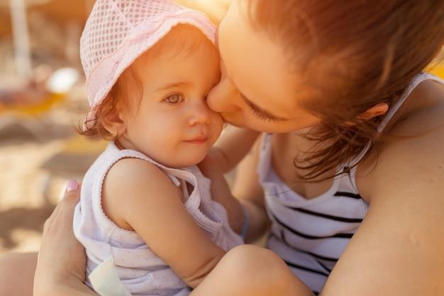 Madre abrazando con su pequeña hija al aire libre en la naturaleza en un día soleado