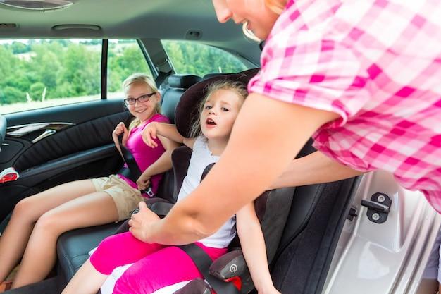 Madre abrochando al niño en un asiento de seguridad