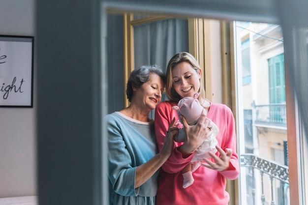 Madre y abuela mirando a bebé