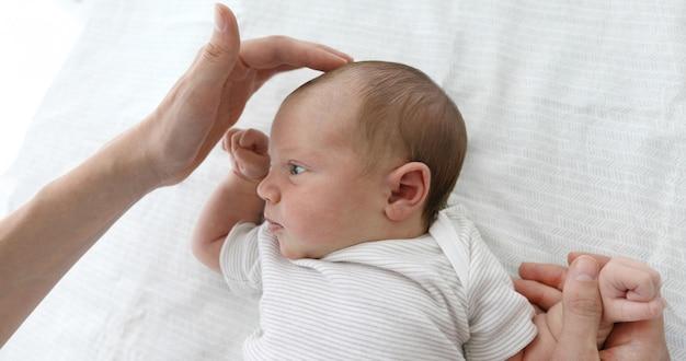 Madre acariciando al niño para sentir la fontanela.