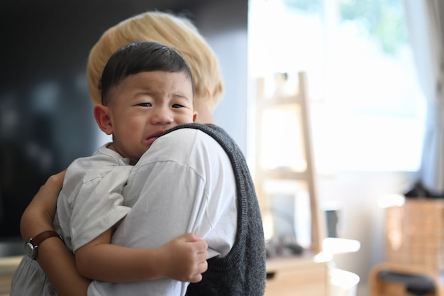 Madre acariciando y calmando a su hijo llorando mientras está de pie en la sala de estar