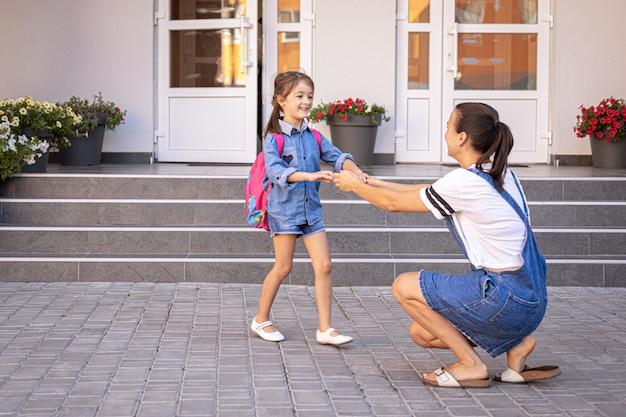 Una madre acompaña al estudiante a la escuela, una niña feliz con una madre cariñosa, de regreso a la escuela.