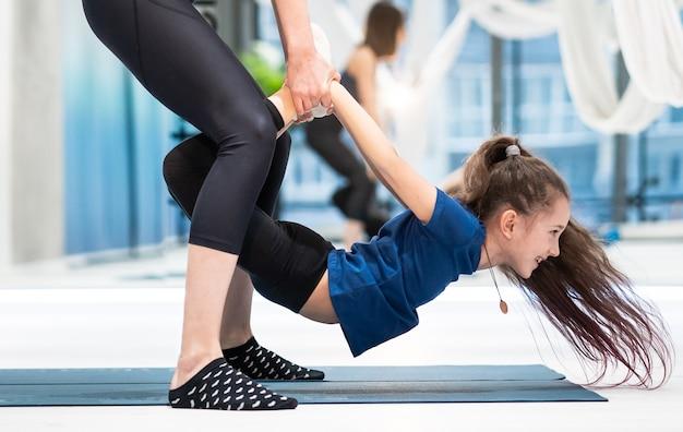 Madre adulta joven ayudando a su hija a hacer el ejercicio
