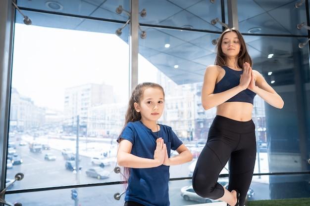 Madre adulta joven y pequeña hija juntas practicando yoga