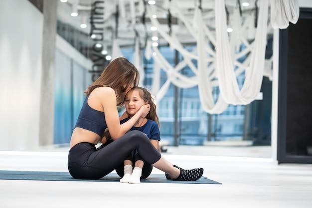 Madre adulta joven recompensa a su pequeña hija con un beso