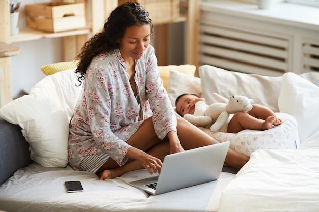 Madre africana multitarea trabajando en casa