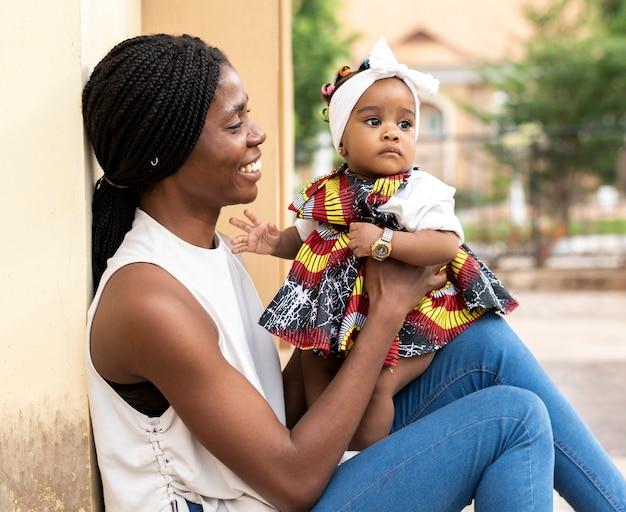 Madre africana, tenencia, niña, tiro medio