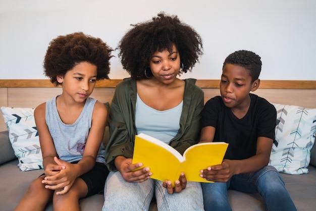 Madre afro leyendo un libro a sus hijos.