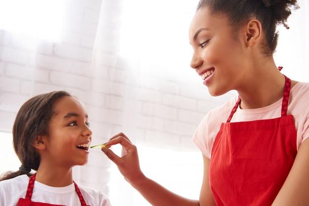 Madre afroamericana está alimentando a su pequeña hija