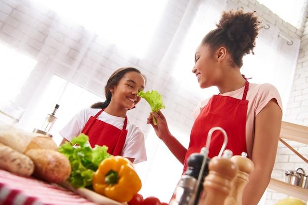 Madre afroamericana en un delantal se alimenta