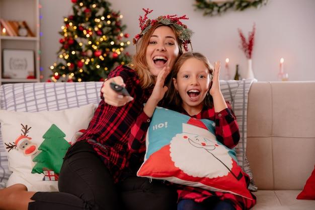 Madre alegre con corona de acebo sostiene control remoto de tv con hija sentada en el sofá y disfrutando de la navidad en casa