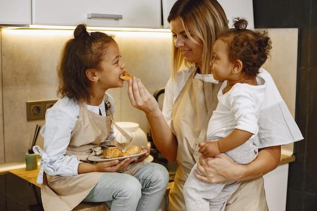 Madre alegre e hija pequeña comiendo galletas recién horneadas en la cocina, disfrutando de la repostería casera, vistiendo delantales y sonriendo el uno al otro, divirtiéndose en casa. madre sosteniendo a su hija pequeña.