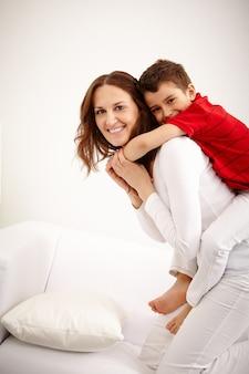Madre alegre llevando al niño pequeño en la espalda