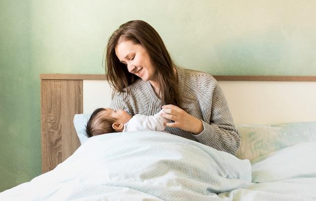 Madre alegre que celebra al bebé en brazos en cama