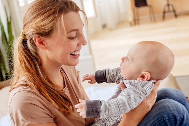 Madre alegre que celebra al niño en casa