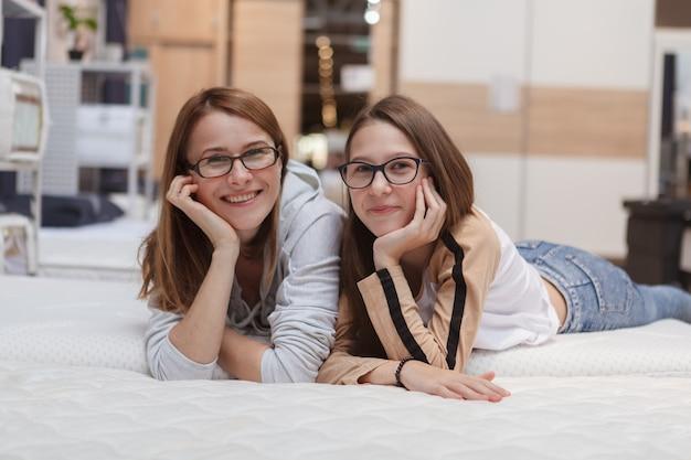 Madre alegre y su hija adolescente acostada en la cama ortopédica