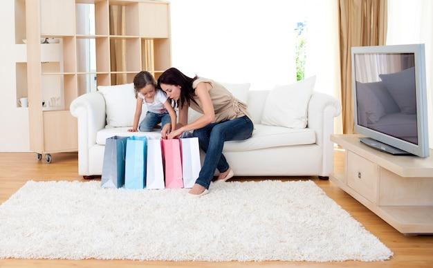 Madre alegre y su hija en casa después de ir de compras