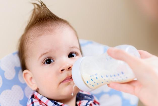 La madre alimenta al bebé con un biberón de leche