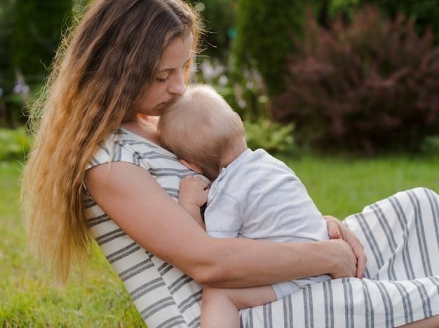 La madre alimenta a su bebé en el campo a la luz del sol al atardecer. lactancia.