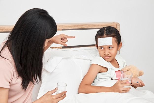 Madre alimentación jarabe de medicina para niña