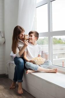 Madre alimentando palomitas de maíz a su hijo sentado cerca del alféizar de la ventana en su casa