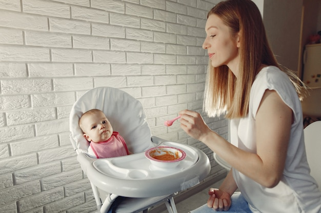 Madre alimentando a su pequeño bebé en una cocina