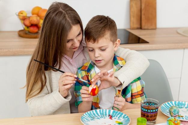 Madre de alto ángulo ayudando a hijo a pintar huevos