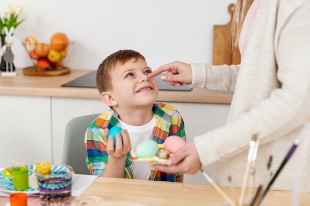 Madre de alto ángulo con hijo haciendo huevos para pascua