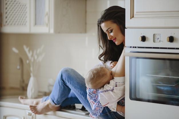 Madre está amamantando en la cocina