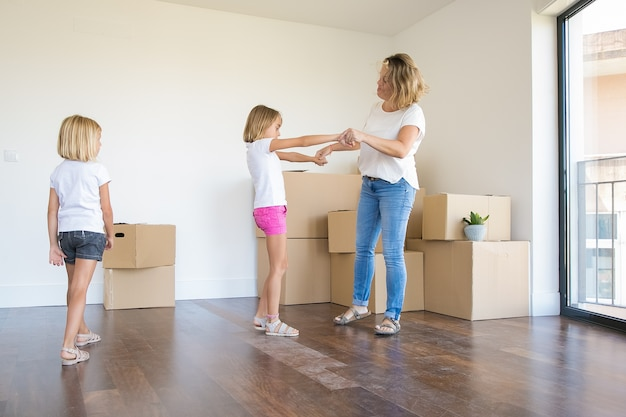 Madre amorosa divirtiéndose y bailando con la hija de un niño en edad preescolar en el nuevo hogar