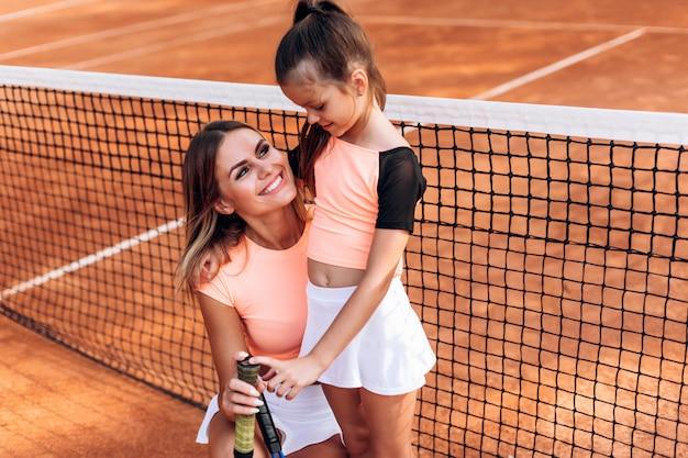 Madre amorosa sostiene a su hija y raquetas de tenis
