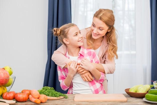 Madre amorosa y su hija de pie detrás de la mesa con verduras