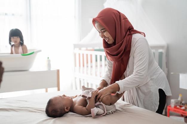Madre aplicando aceite de bebé a su bebé