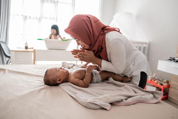 Madre aplicando aceite a su bebé