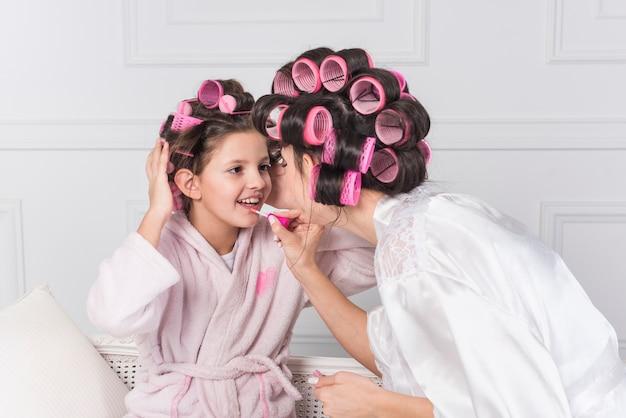 Madre aplicando brillo de labios brillante en labios de hijas