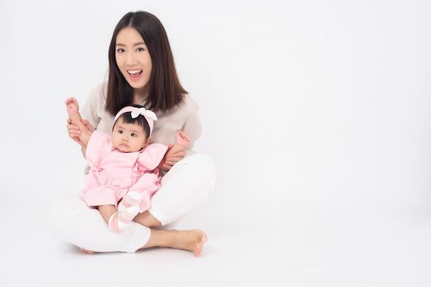 Madre asiática y adorable niña son felices en la pared blanca