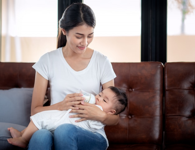 Madre asiática alimentando con leche a su bebé por biberón