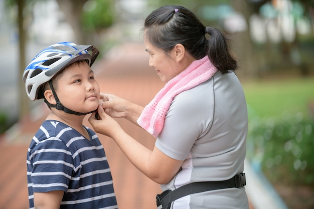 Madre asiática ayudando a su hijo usa casco azul