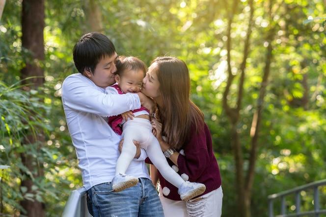 Madre asiática con padre llevando y besando a la hija en el bosque, concepto de familia y amor