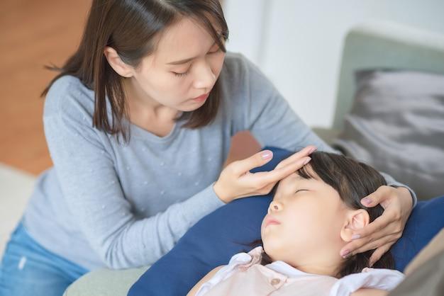 Madre asiática cuida a su hijo que tiene fiebre y enfermedad en casa.