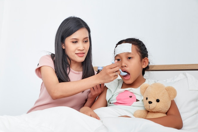 Madre asiática cuidar hija enferma en la cama
