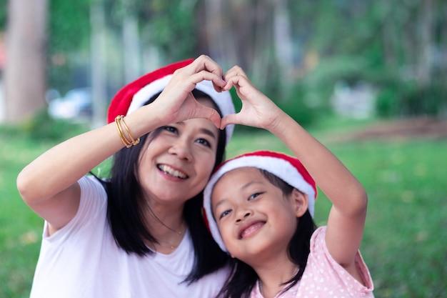 Madre asiática e hija que hacen el corazón de la mano en el día de la navidad o