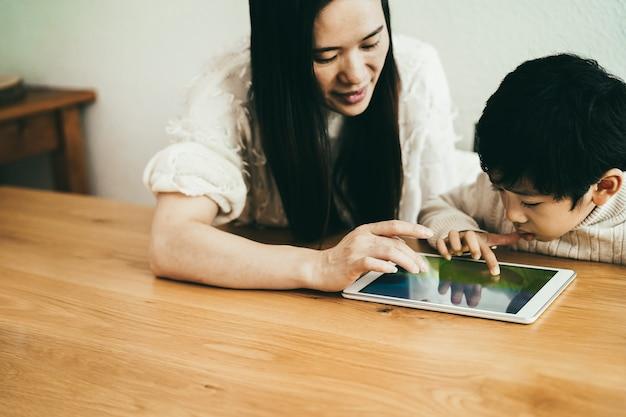 Madre asiática e hijo pequeño jugando videojuegos con tableta en interiores en casa