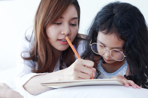 Madre asiática está enseñando a su hija la tarea en casa