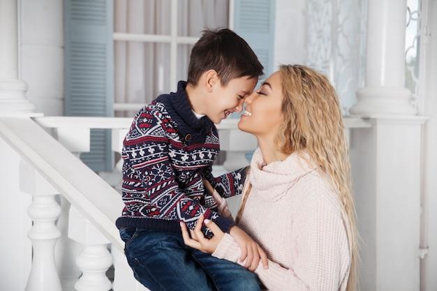 Madre asiática hermosa que abraza con su pequeño hijo en el pórche de entrada blanco de una casa de vacaciones del país.